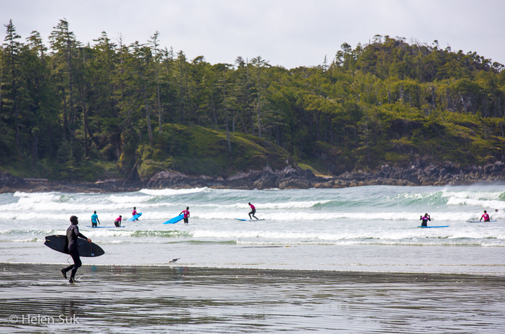 surfers on the beach in tofino bc