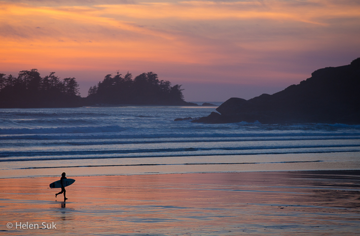 a surfer walks across the beach at sunset on cox bay beach tofino