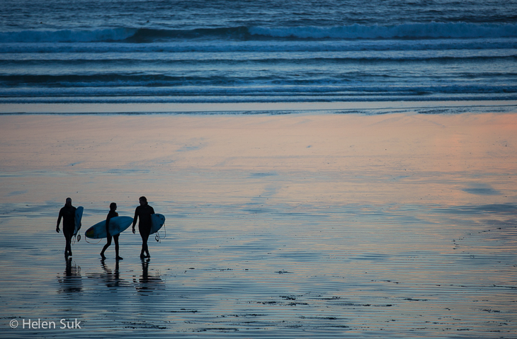 silhouette of three surfers at sunset in tofino canada