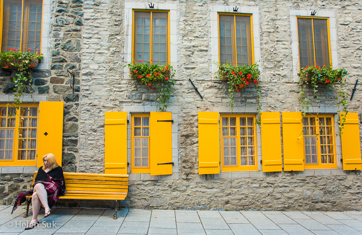 woman sits on a bench in front of yellow shutters in old quebec city