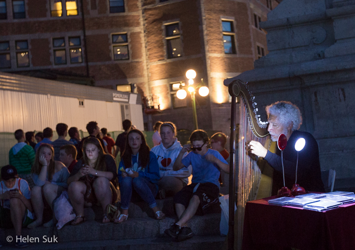 man plays a harp for visitors in old quebec city