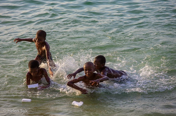boys splashing in the water at the seafront in stone town zanzibar