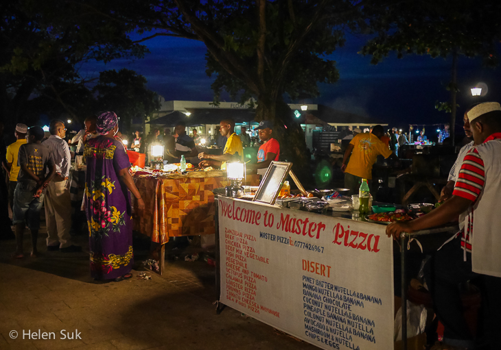 locals gather at food stalls at Forodhani Gardens, an outdoor night market in Stone Town Zanzibar