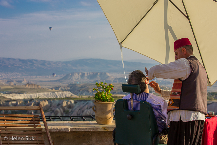 turkish barber shaves a man on the terrace at the museum hotel