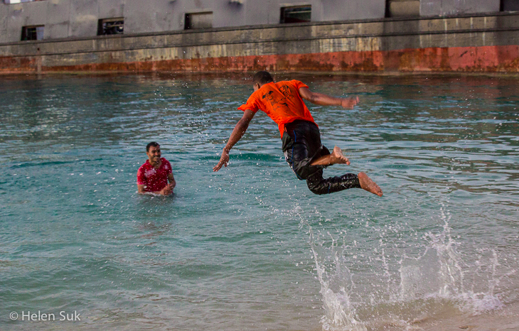 picture of a boy leaping into the water in stone town