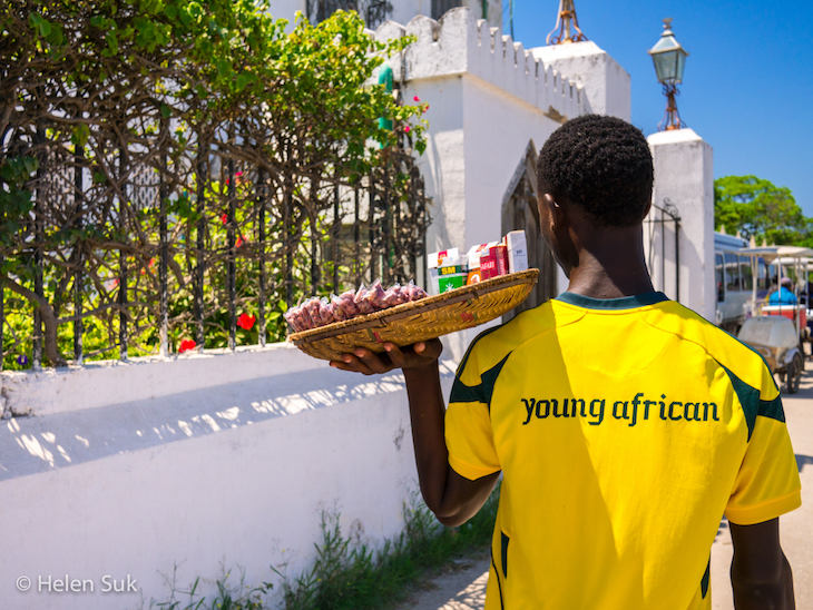 young african man selling cigarettes in stone town