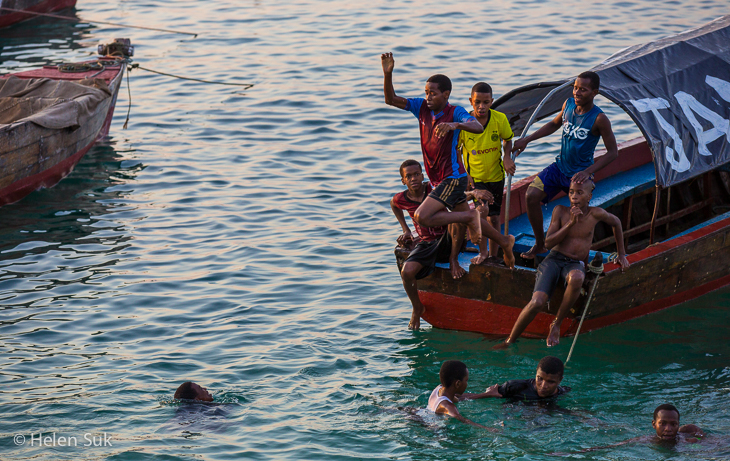 zanzibar picture of local boys playing in the water at the seafront in stone town