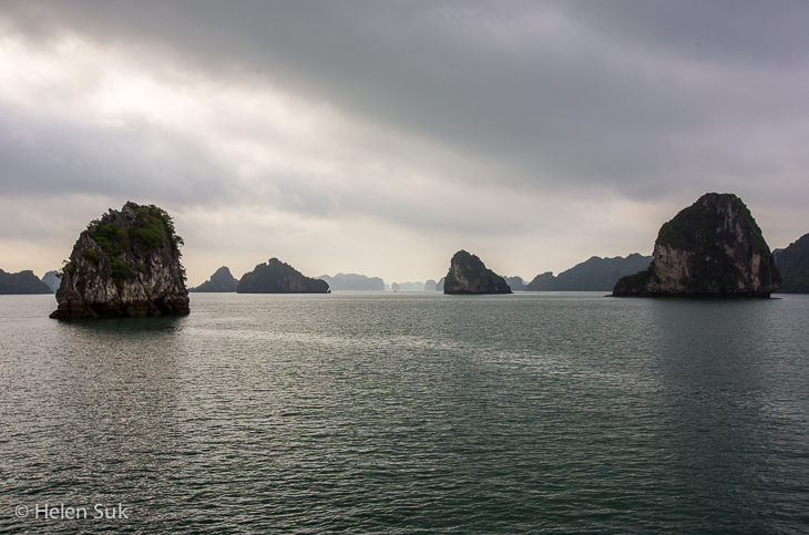 limestone karsts strewn across bai tu long bay in a dark and moody setting