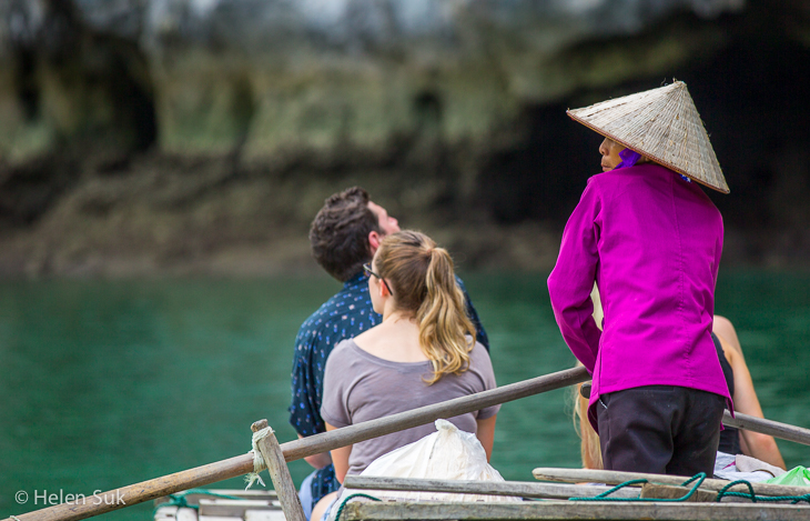 vietnamese woman driving a small boat with tourists in vung vieng village in halong bay