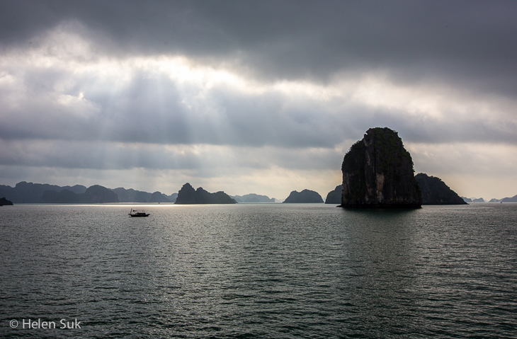 local boat sails across moody bai tu long bay vietnam under dark clouds