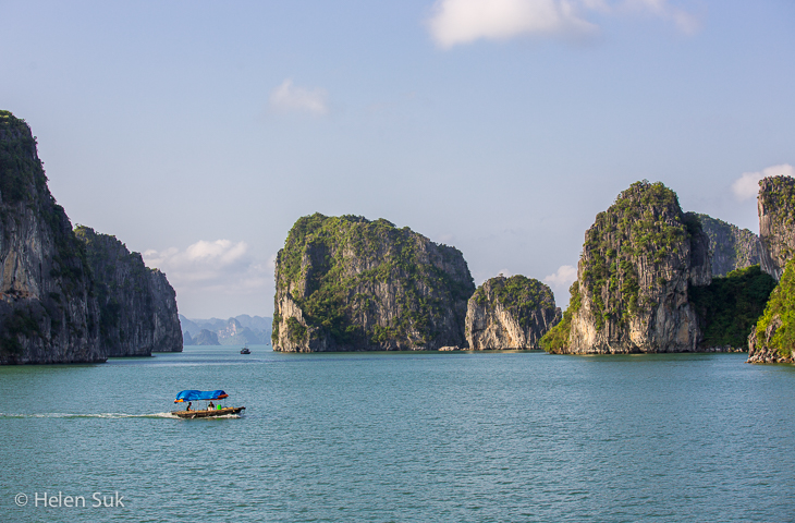local boat sails across bai tu long bay, vietnam