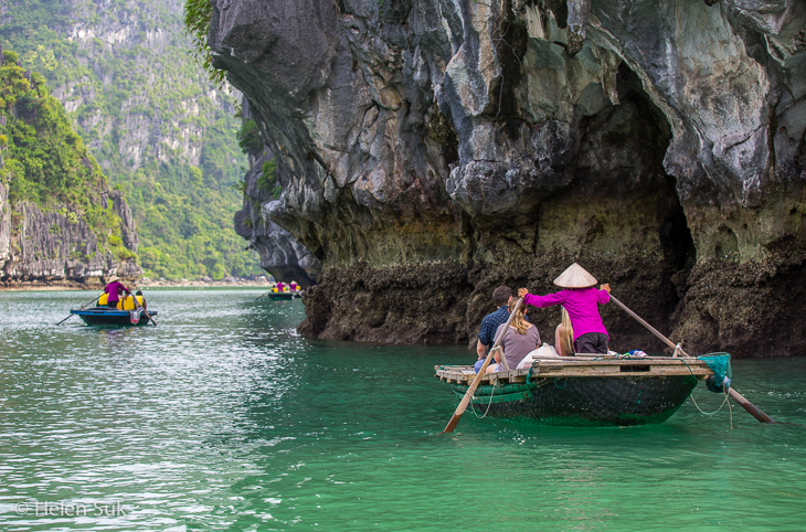 small wooden boats with tourists floating through vung vieng village in bai tu long bay