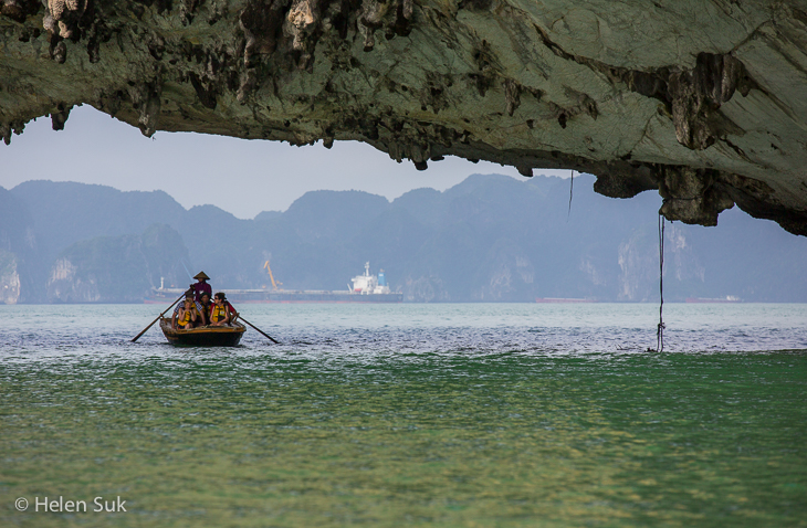 small boat floats under a limestone karst in halong bay