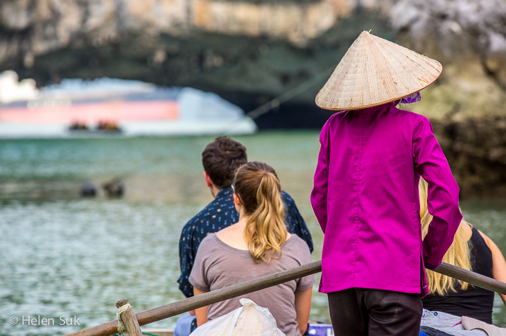 vietnamese women taking tourists on a boat through a fishing village in bai tu long bay