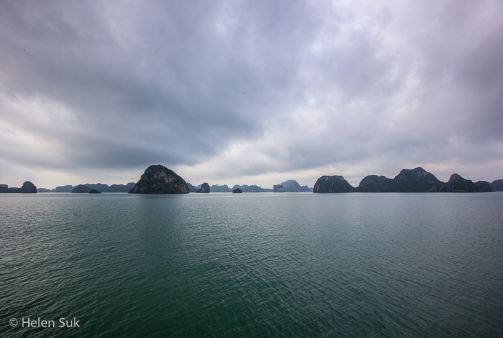 limestone karsts strewn across bai tu long bay in halong bay in a dark and moody setting