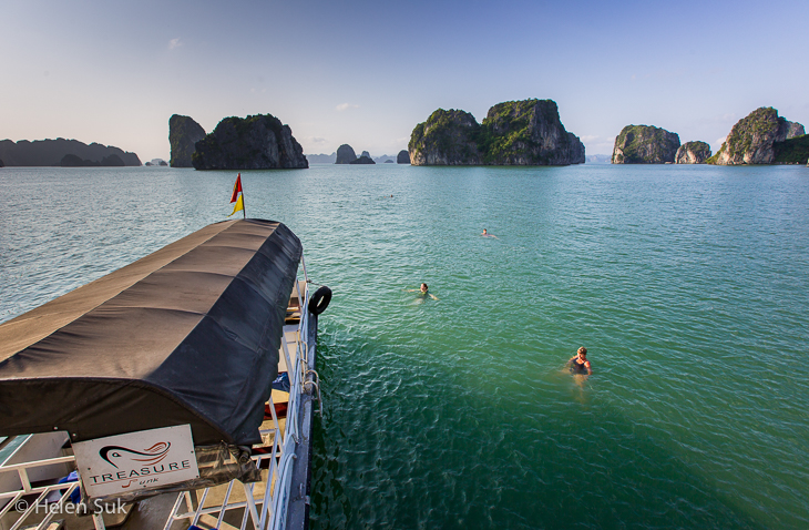treasure junk, passengers swimming in the emerald waters of bai tu long bay vietnam