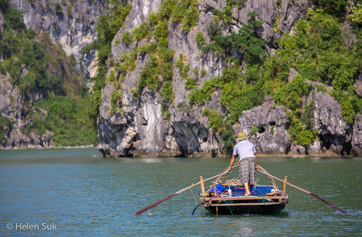 man rows a boat through vung vieng village in bai tu long bay vietnam