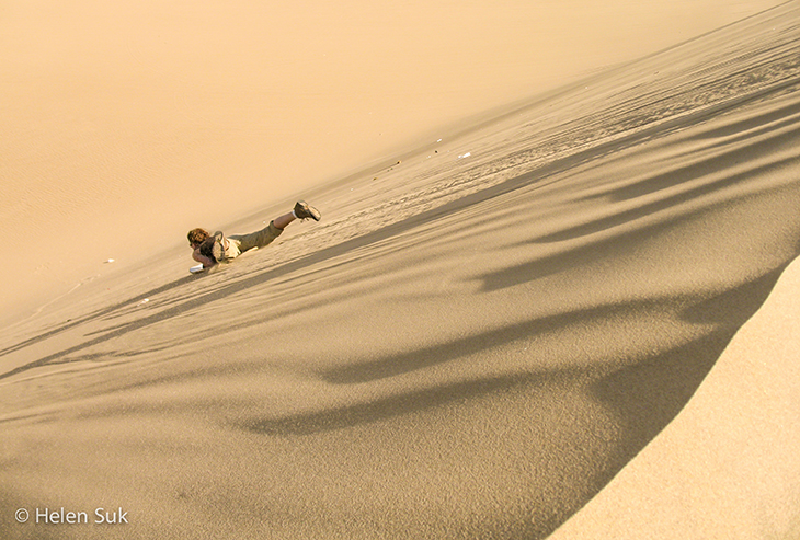 woman sandboards down a dune in huacachina peru