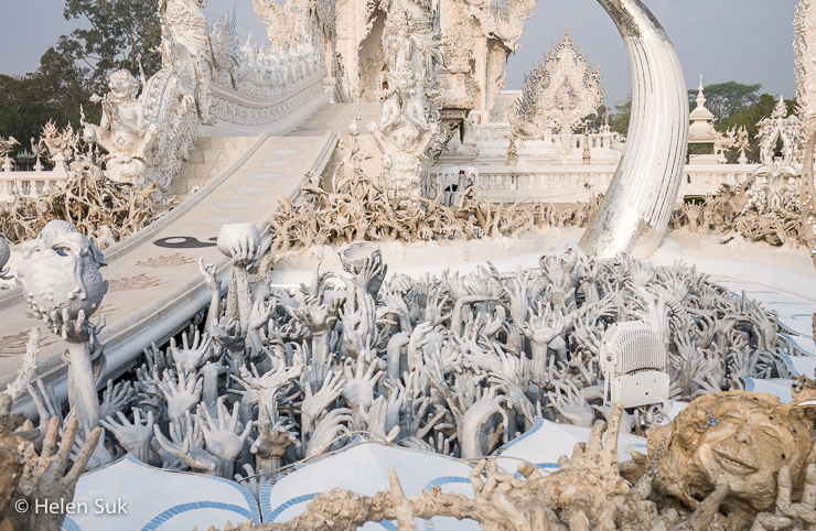 ghostly hands extend from the sea of suffering at wat rong khun in chiang rai thailand