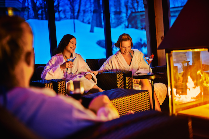 friends relax over drinks in front of a crackling fire in the lounge at nordik spa chelsea