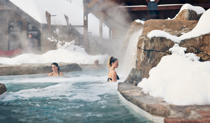 two women immerse themselves in a hot outdoor bath at nordik spa in gatineau quebec