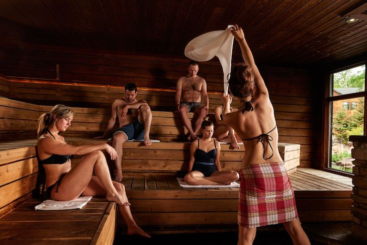 woman performs the aufguss ritual of swinging a towel inside a sauna