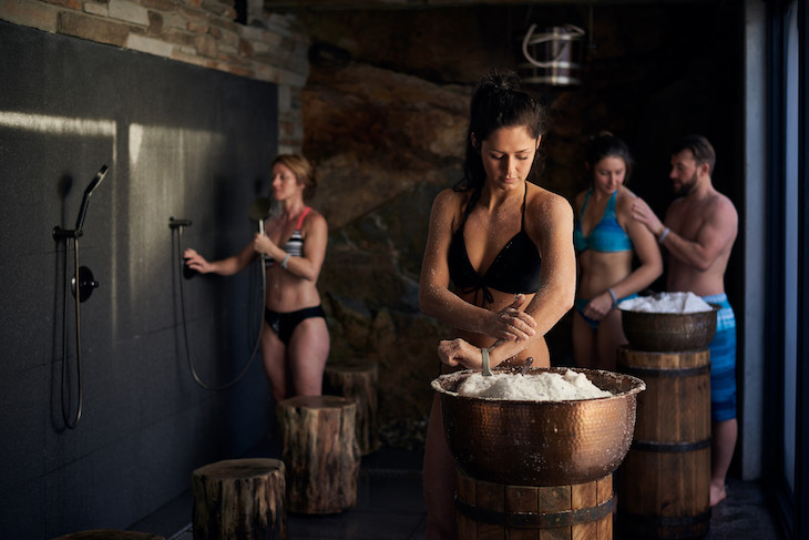 women scrub themselves with salt at the scrub station at nordik spa