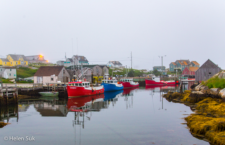 boats in the harbour at peggys cove on a foggy day